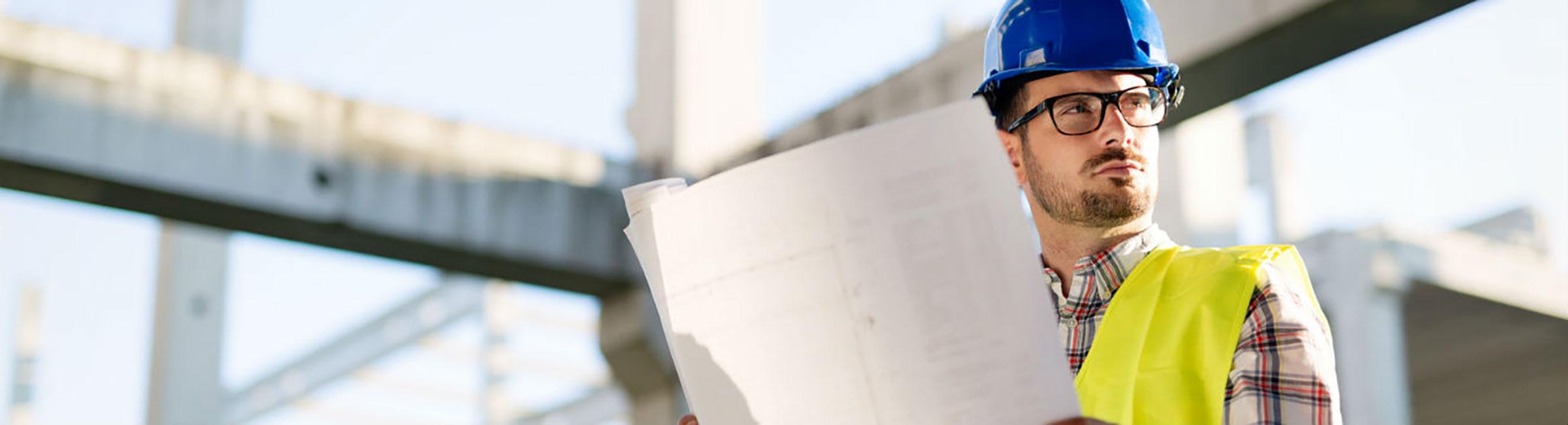 Homme lit un plan et travaille dans le secteur du bâtiment